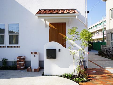江戸川区で自然素材の注文住宅を建てるニットー住宅 白い壁とレンガのアクセントが映える自慢の外観デザインを