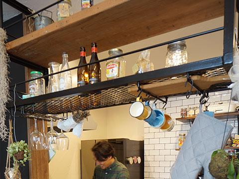 江戸川区で自然素材の注文住宅を建てるニットー住宅 カウンターキッチンの上部にアイアンで作られたおしゃれな調味料が揃う収納棚