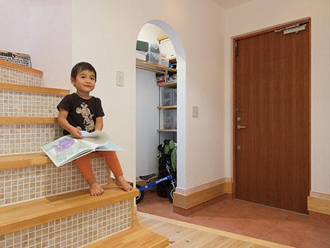 江戸川区で自然素材の注文住宅を建てるニットー住宅 広々とした土間玄関からすぐにある蹴上がタイルで仕上げられた階段